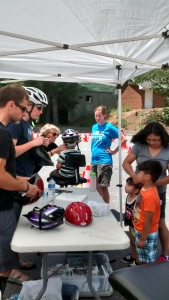 Clinton Marsh and Kim Marland help fit kids with bike helmets at the bike rodeo.